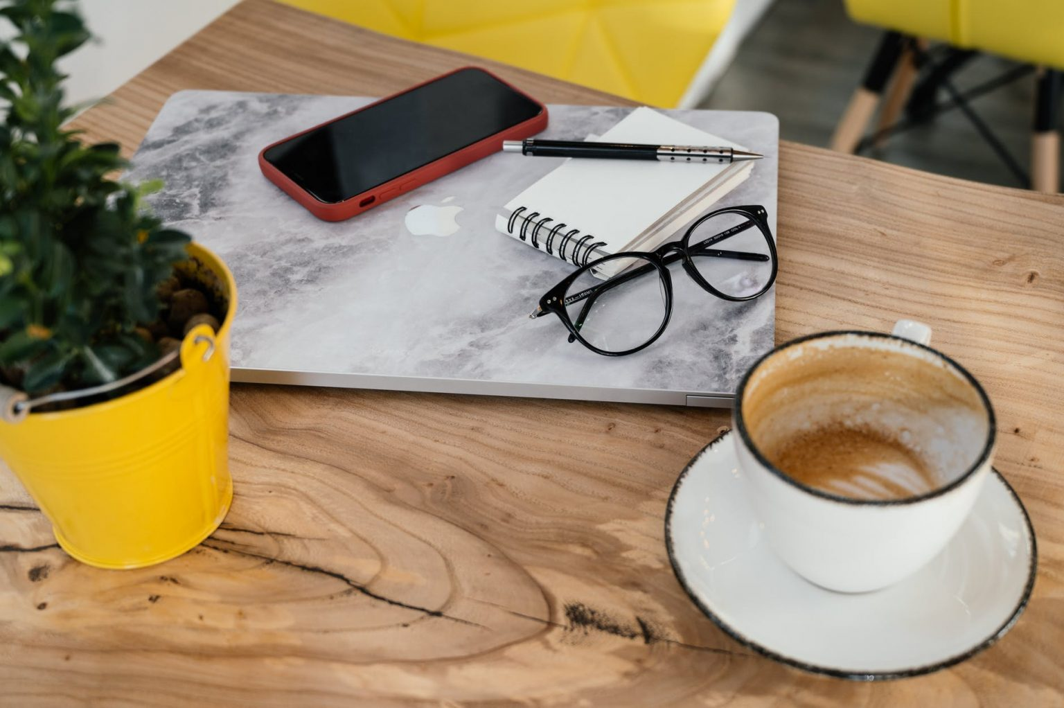 modern gadgets placed on table with cappuccino in cafeteria